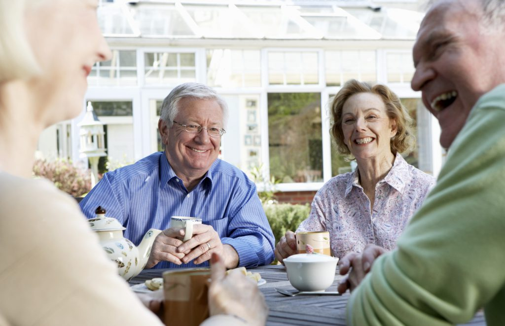 Two senior couples having tea outdoors (focus on couple in background)