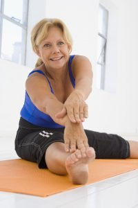 Smiling woman stretching on exercise mat